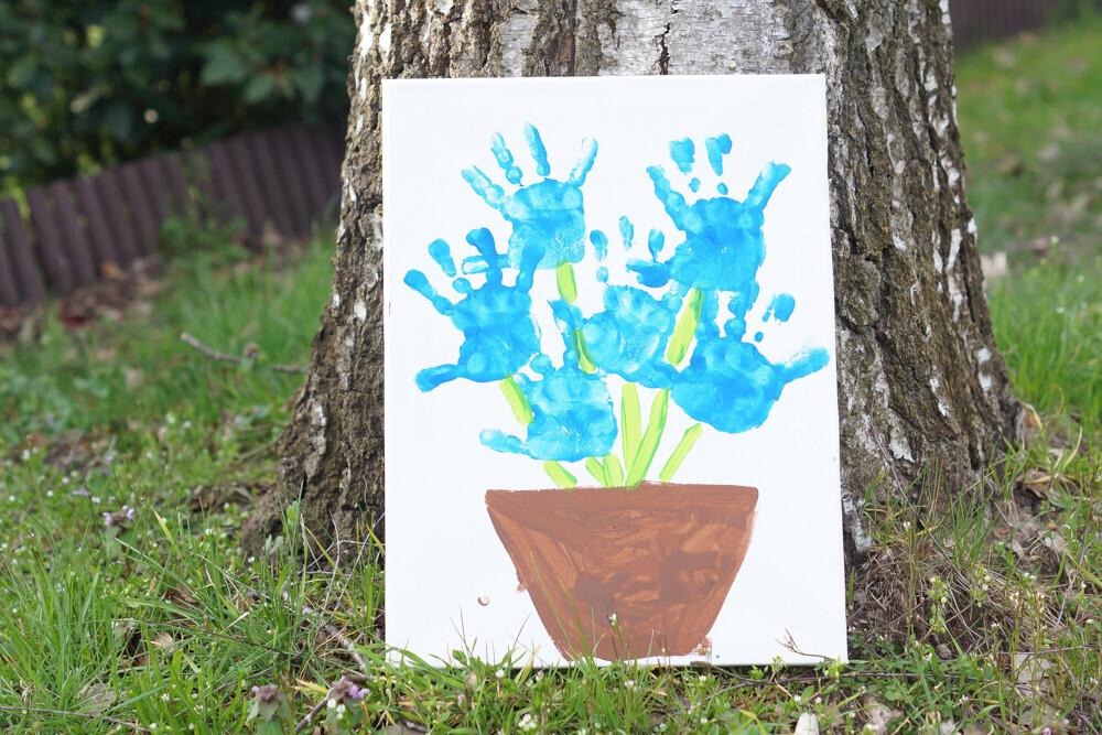 une toile sur le printemps faite en empreinte de mains pour créer un bouquet de fleurs
